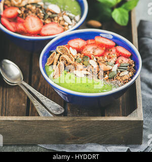 Green smoothie bowls with seeds, nuts and fruit, square crop - Stock Photo
