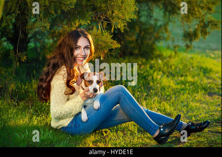 Young beautiful girl is dying and sits with her pet Jack Russell Terrier on the green grass - Stock Photo