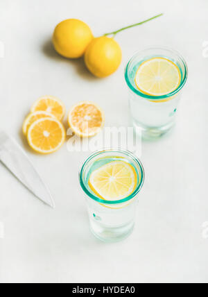 Detox lemon water in glasses served with fresh lemon fruits - Stock Photo