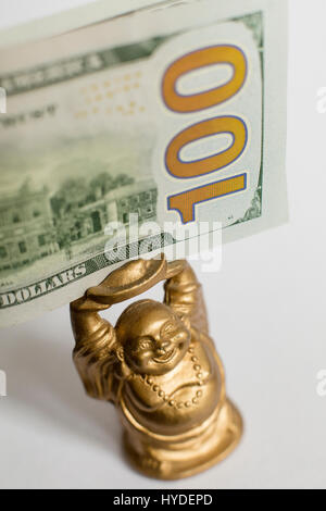 a small golden buddha figurine standing on a white back ground holds a one hundred dollar bill in United States - Stock Photo