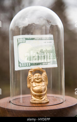 a small golden buddha figurine standing in a glass display dome holds a folded one hundred dollar bill above his - Stock Photo