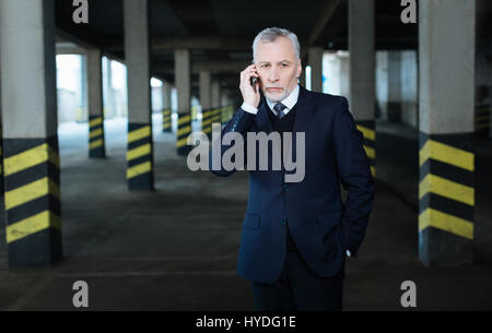 Making a call. Serious nice good looking businessman putting his hand to the pocket and holding his smartphone while - Stock Photo