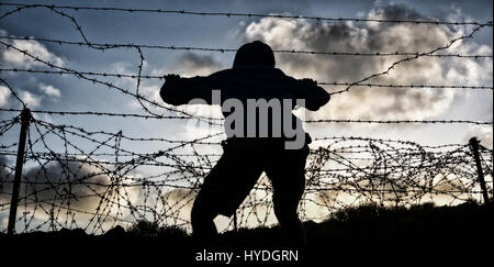 Brexit, immigration, asylum seekers... concept image. Rear view of man looking through barbed wire fence - Stock Photo