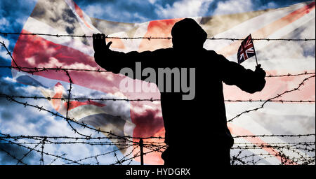 Brexit, immigration, asylum seekers... concept image. Rear view of man looking through barbed wire fence; Union - Stock Photo