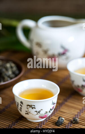 Hand rolled Chinese Pearl Jasmine Tea in traditional tea set - Stock Photo