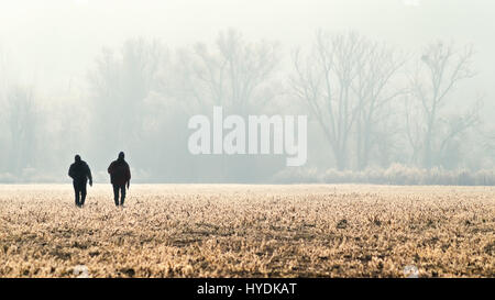 Panorama with silhouette of the two hunters, photographer, hikers or tourists on the field at sunrise. Group of - Stock Photo