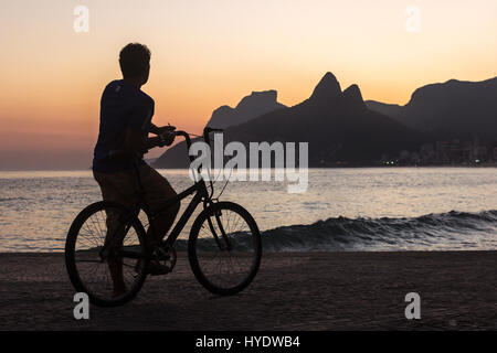 Man on a bicycle watching the sunset behind Dois Irmãos rock on Ipanema beach - Stock Photo