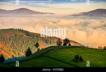 mountain rural area in autumn season. agricultural field with fence and haystack on a hillside. deep fog down in - Stock Photo
