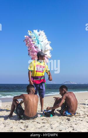 Brazil, Rio de Janeiro: Man that sells cotton candy with friends on Copacabana beach - Stock Photo