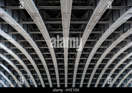 Detail of riveted steel beams supporting span of bridge crossing the River Thames - Stock Photo