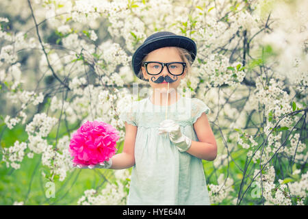 Funny girl in hat and gloves and with fake mustache. - Stock Photo