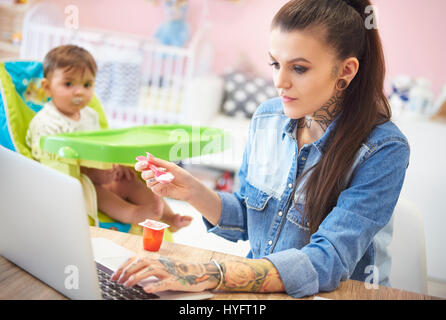 Young mother feeding her baby at home office - Stock Photo