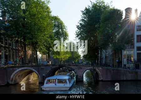 Tourist boat on canal, in summer sunshine, Amsterdam, Netherlands, Europe - Stock Photo