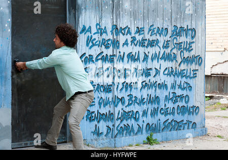 A guy trying to open a door near a mural in the roman neighbourhood Primavalle. Rome, Italy. - Stock Photo