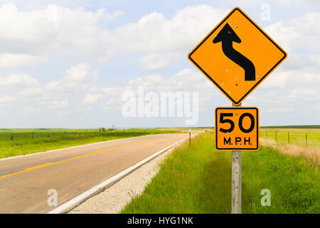 Road signs displaying the maximum speed of 50 mph and that it is a curvy road in the Flint Hills region in Kansas. - Stock Photo