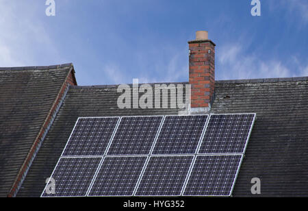 Solar panels on sloped roof top covered with roof tiles with blue sky in background in Stoke on Trent,Staffordshire,UK.Solar - Stock Photo