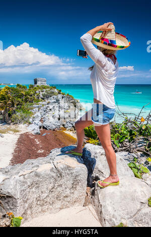 Woman with a straw hat taking photo of  Mayan ruins in Tulum, Mexico - Stock Photo