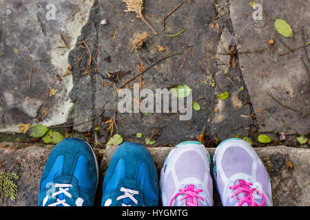 top view of a two pairs of sneakers shoes on paving stone - Stock Photo
