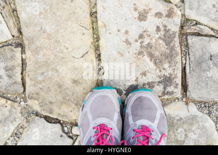 top view of pair of sneakers shoes on paving stone - Stock Photo
