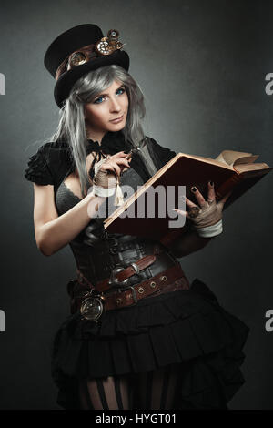 Steampunk scientist with open book and magnifying lens - Stock Photo