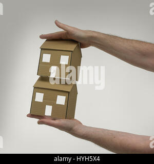 Two Cardboard Houses held in hands. - Stock Photo
