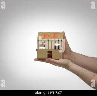 Cardboard House held in hands with fragile stamp. - Stock Photo