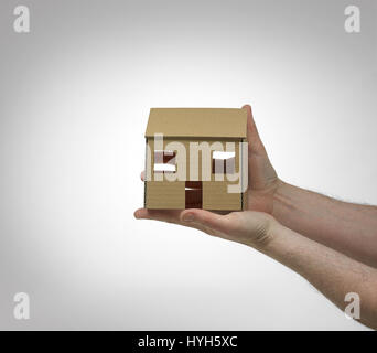 Cardboard House held in hands. - Stock Photo