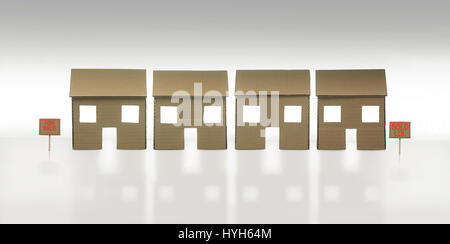 Row of Cardboard Houses, one for sale and one sold - Stock Photo
