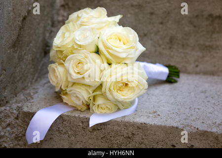 Wedding bouquet laid on a concrete stairs - Stock Photo