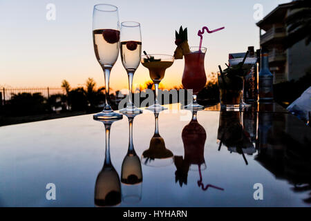 Cocktails at an outside bar at sunset in the warm sunshine - Stock Photo