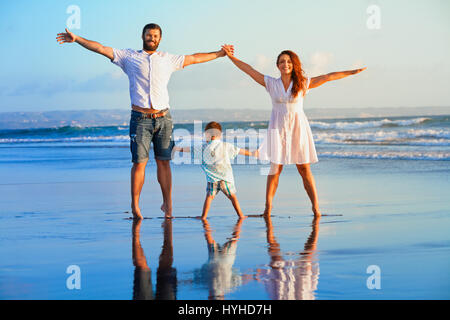 Happy family - father, mother, baby son hold hands, walk and jump together by water pool on sunset black sand beach - Stock Photo