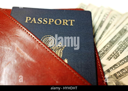 USA passport with US currency in leather travel document holder - Stock Photo