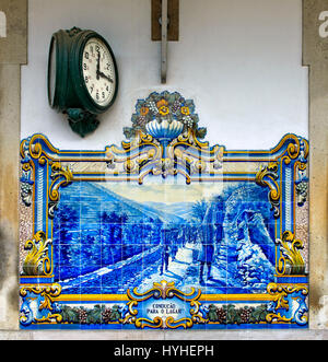 Station clock and hand-painted ceramic tiles, azulejos, at the Pinhao train station depicting scenes of the grape - Stock Photo