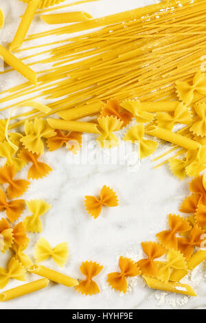 Various types of pasta on a white marble table with flour - Stock Photo