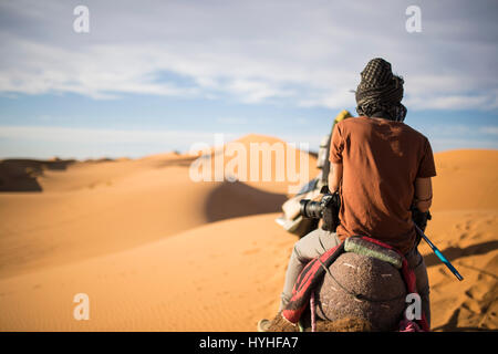 Tourist on a camel going through the sand dunes in the Sahara Desert at sunset - Morocco. - Stock Photo