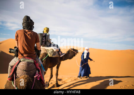 Tourists on camels going through the sand dunes in the Sahara Desert at sunset - Morocco. - Stock Photo
