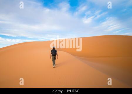 A man walks on the dunes in the Sahara Desert at sunset - Merzouga - Morocco - Stock Photo