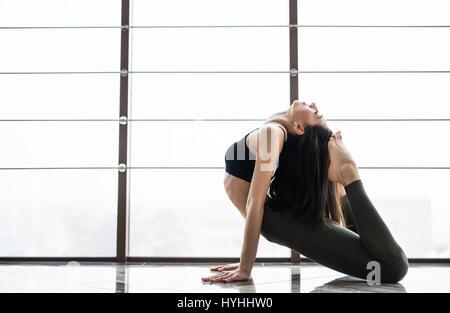 Young slim blond woman in yoga class making beautiful asana exercises. Girl do mermaid pose, variation of rajakapotasana. - Stock Photo