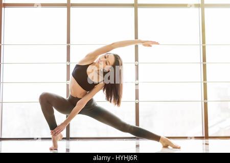 Beautiful sporty fit yogini woman practices yoga asana Anjaneyasana - Stock Photo