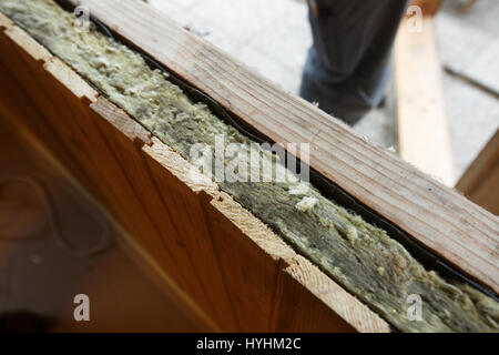 Exposed drywall insulation during window change in an old wooden house. Home renovation, sustainable living, energy - Stock Photo