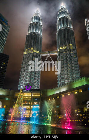 Petronas Towers and the Fountains at night during christmas - Stock Photo