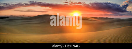 Wide panorama of deserted sand dunes at colourful sunrise over distant horizon. Untouched sand drawings lit by rays - Stock Photo