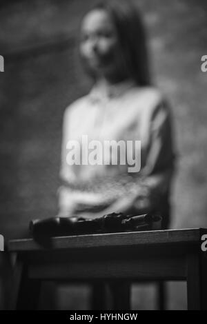Alarmed scared hostage looking at gun - Stock Photo