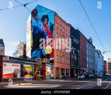 Berlin, Mitte. Mural  Mercedes-Benz advertisement. Painting by commercial artists on scissor lift - Stock Photo