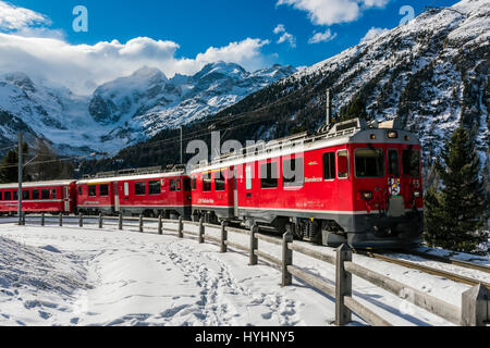 Winter view of Bernina Express red train with Bernina and Morteratsch Glacier in the background, Graubunden, Switzerland - Stock Photo