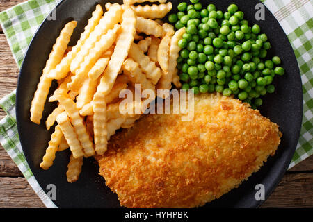 Delicious cod fish and chips with peas close-up on a plate on the table. Horizontal view from above - Stock Photo