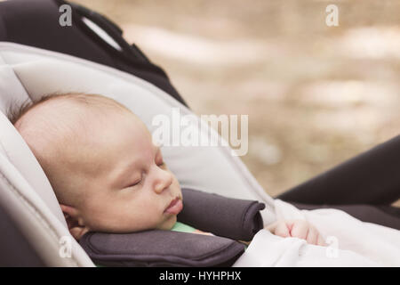 Baby boy fastened with security belt is sleeping peacefully in the car safety seat on the blur brown background, - Stock Photo
