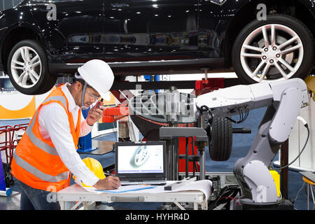 Automotive engineer with assistance robotic inspect modern car, Industry 4.0 concept - Stock Photo