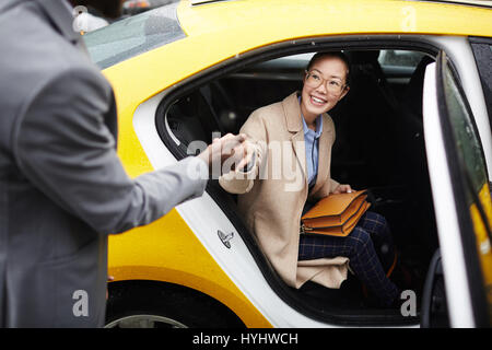 Gentleman Helping Young Woman Leave Taxi - Stock Photo