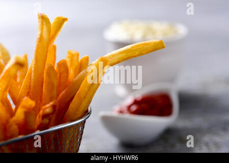 closeup of some appetizing french fries served in a metal basket and some bowls with mayonnaise and ketchup in the - Stock Photo